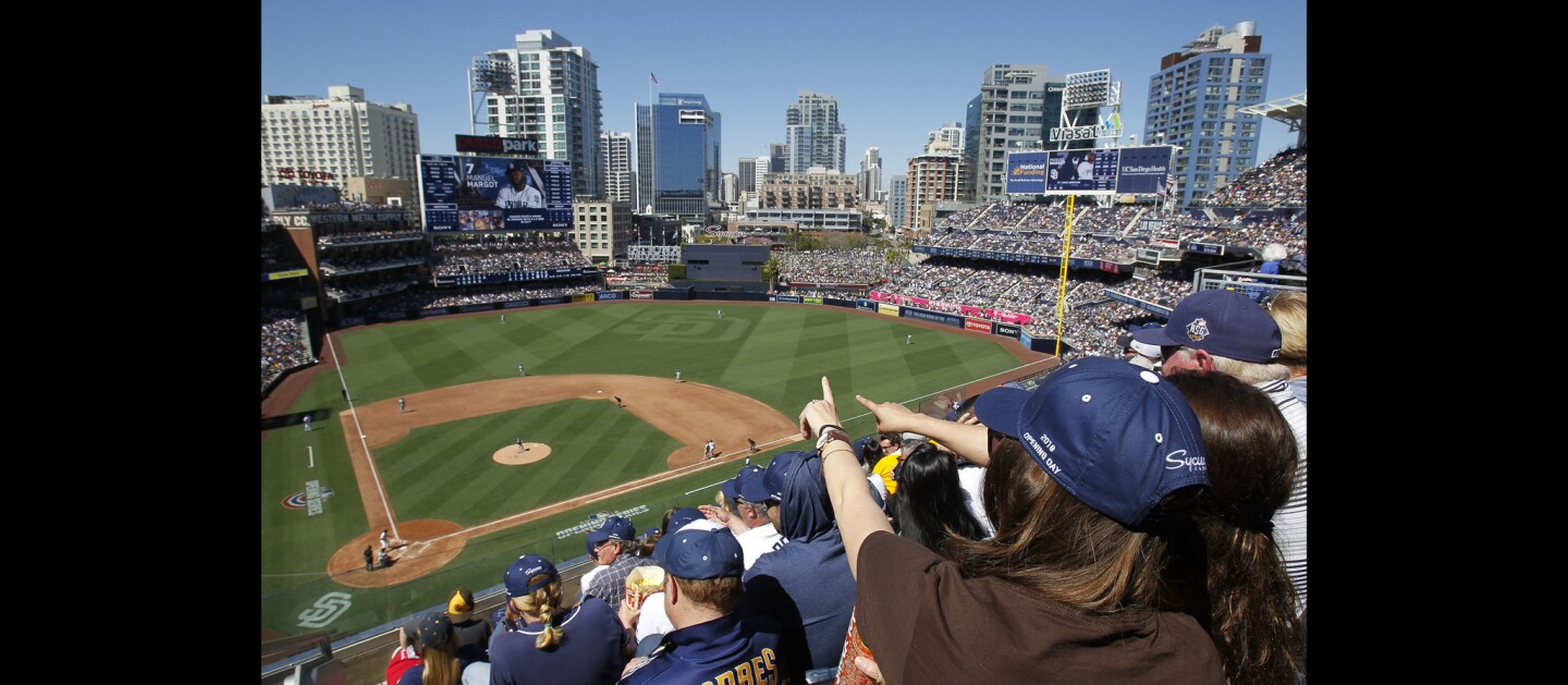 Padres fans Alex Stephens, left, and Cristina Velasco point as they watch the Padres play the Milwaukee Brewers on Opening Day.