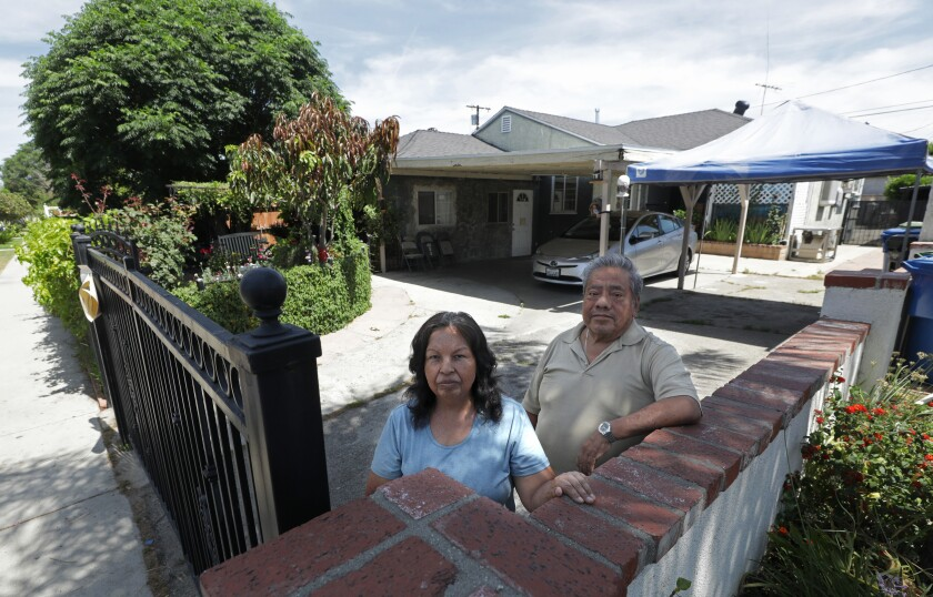 Josefina and Marcelino Rodriguez in front of the home they are afraid they will lose.