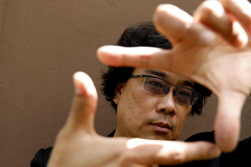 Bong Joon Ho holding his thumbs and forefingers in front of his face in the shape of a frame.