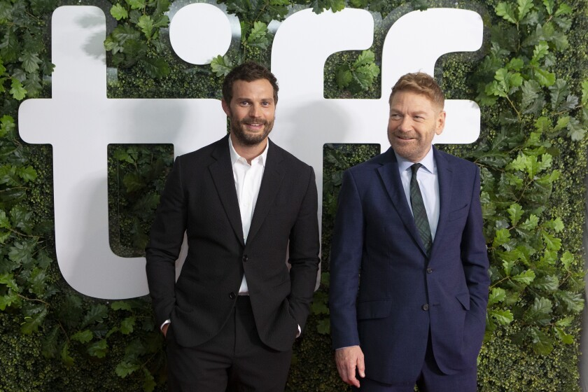"""Director Kenneth Branagh, right, and actor Jamie Dornan walk the red carpet as they promote the film """"Belfast"""" during the Toronto International Film Festival, in Toronto, Sunday, Sept. 12, 2021. (Chris Young/The Canadian Press via AP)"""