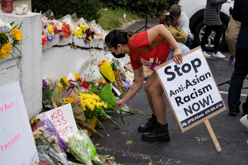 """A person holding a """"Stop Anti-Asian Racism Now!"""" sign leaves flowers at a memorial"""