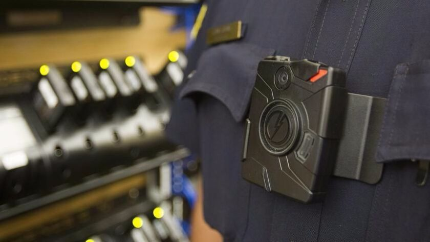 A police officer wearing a body camera stands in front of a recharging station.
