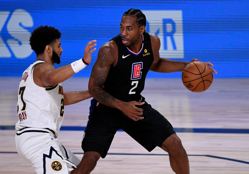 Kawhi Leonard #2 of the LA Clippers drives the ball against Jamal Murray.