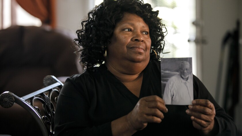 Rosie Harmon holds a photo of brother Bobby Joe Maxwell, whose 1984 murder convictions were overturned decades later.