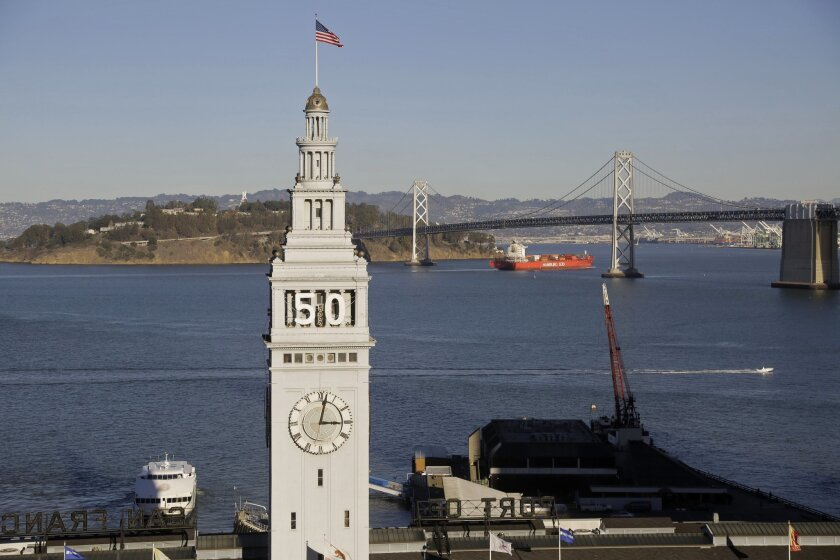 In this photo taken Wednesday, Dec. 16, 2015, is the Ferry Building in San Francisco. In the background is the San Francisco-Oakland Bay Bridge. Atop the waterfront tower is the number 50 for the upcoming Super Bowl in February 2016. Located beginning Jan. 30 in front of the Ferry Building will be Super Bowl City where Market Street meets the Embarcadero and will be a free walk-around area that will be the broadcast home for CBS. (AP Photo/Eric Risberg)
