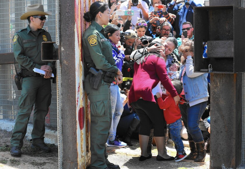 Border Patrol agents watch as members of selected families that have been separated for years reunite — however briefly — at the Door of Hope at Border Field State Park near San Diego. This is the third year for Children's Day.