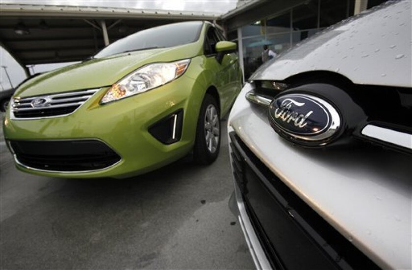In this Wednesday, Aug. 31, 2011 photo, a Lime Squeeze Metallic 2012 Ford Fiesta SE, left, and an Ingot Silver Metallic 2012 Ford Focus Titanium 5-Door Hatchback are shown at the Maroone Ford of Miami dealership in Miami. Ford, GM and Chrysler saw their combined share of the U.S. market rise by 200,000 cars and trucks between the end of 2010 and November, 2011. U.S. auto sales are poised for a second straight year of growth in 2012 _ the result of easier credit, low interest rates and pent-up demand for cars and trucks created by the Great Recession. (AP Photo/Wilfredo Lee)