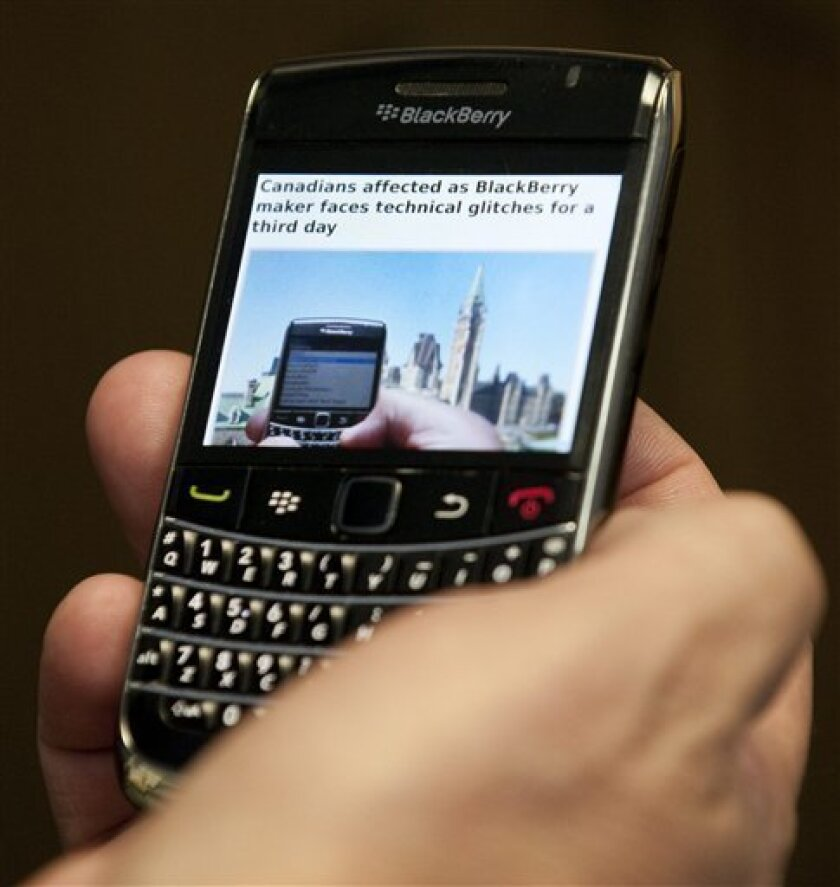A Blackberry subscriber holds a Research in Motion Blackberry in Ottawa, Wednesday Oct.12, 2011. Sporadic outages of BlackBerry messaging and email service spread to the U.S. and Canada on Wednesday, as problems stretched into the third day for Europe, Asia, Latin America and Africa. (AP Photo/The Canadian Press, Adrian Wyld)
