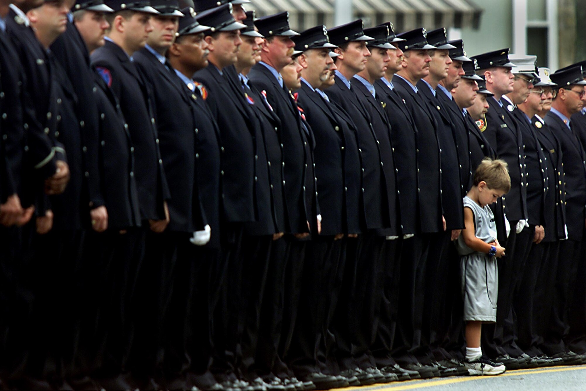 A small boy stands before a long line of firefighters