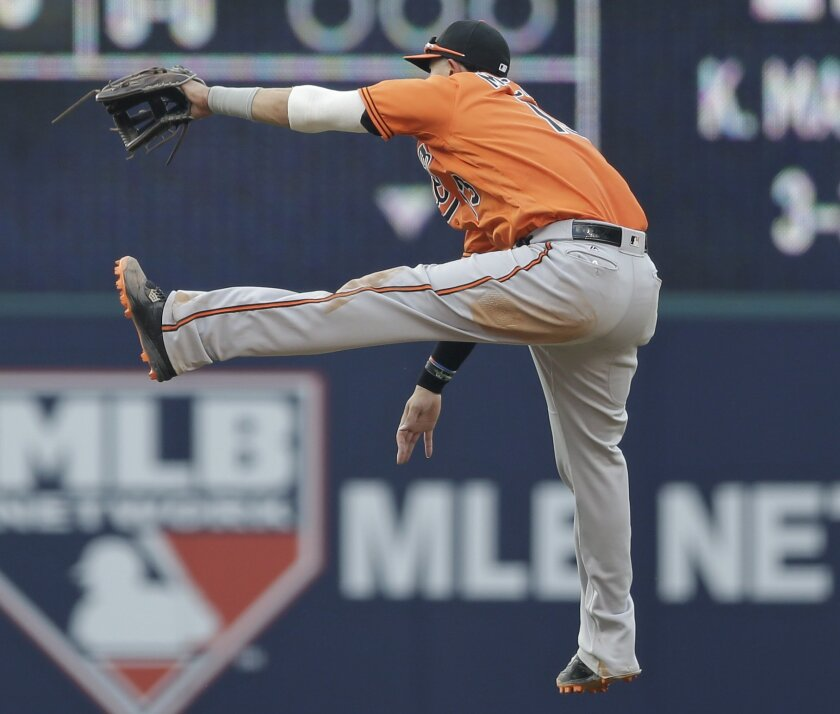 Baltimore Orioles' Manny Machado jumps for but cannot get the ball hit by Cleveland Indians' Yan Gomes in the fifth inning of a baseball game, Saturday, May 28, 2016, in Cleveland. Juan Uribe scored on the play. (AP Photo/Tony Dejak)