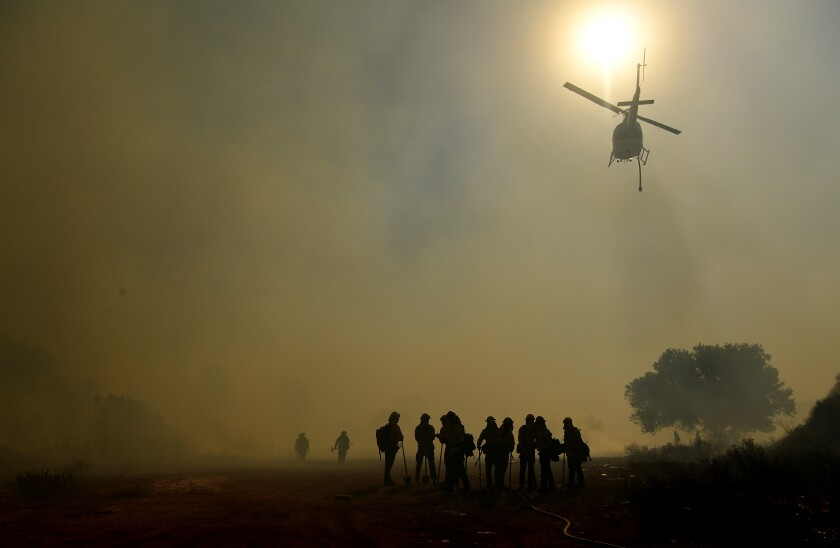 Several firefighters silhouetted in the smoke as a water-dropping helicopter flies overhead