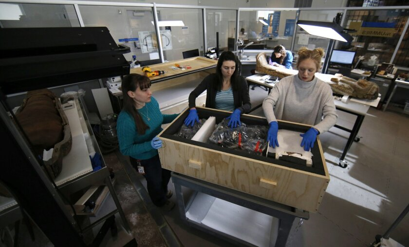 In this Thursday, Jan. 28, 2016, photo, collections technicians Ashley Scott, from left, Severine Craig and Taylor Barrett pack a crate of artifacts at the Penn Museum in Philadelphia. The archaeology museum has moved thousands of ancient treasures offsite and is using vibration sensors to monitor