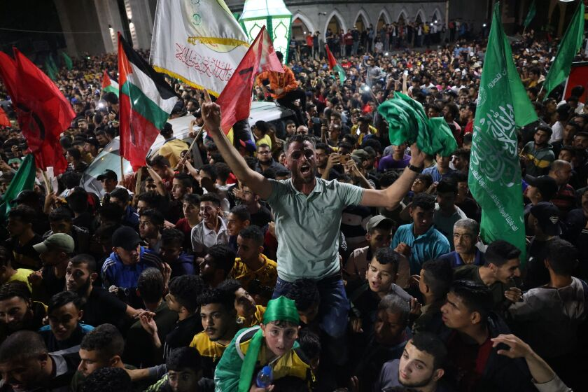 People celebrate in the streets following a ceasefire brokered by Egypt between Israel and the ruling Islamist movement Hamas, in Rafah, in the southern Gaza Strip on May 21, 2021. - A ceasefire between Israel and Hamas, the Islamist movement which controls the Gaza Strip, came into force early on May 21, 2021 after 11 days of deadly fighting that pounded the Palestinian enclave and forced countless Israelis to seek shelter from rockets. (Photo by SAID KHATIB / AFP) (Photo by SAID KHATIB/AFP via Getty Images)