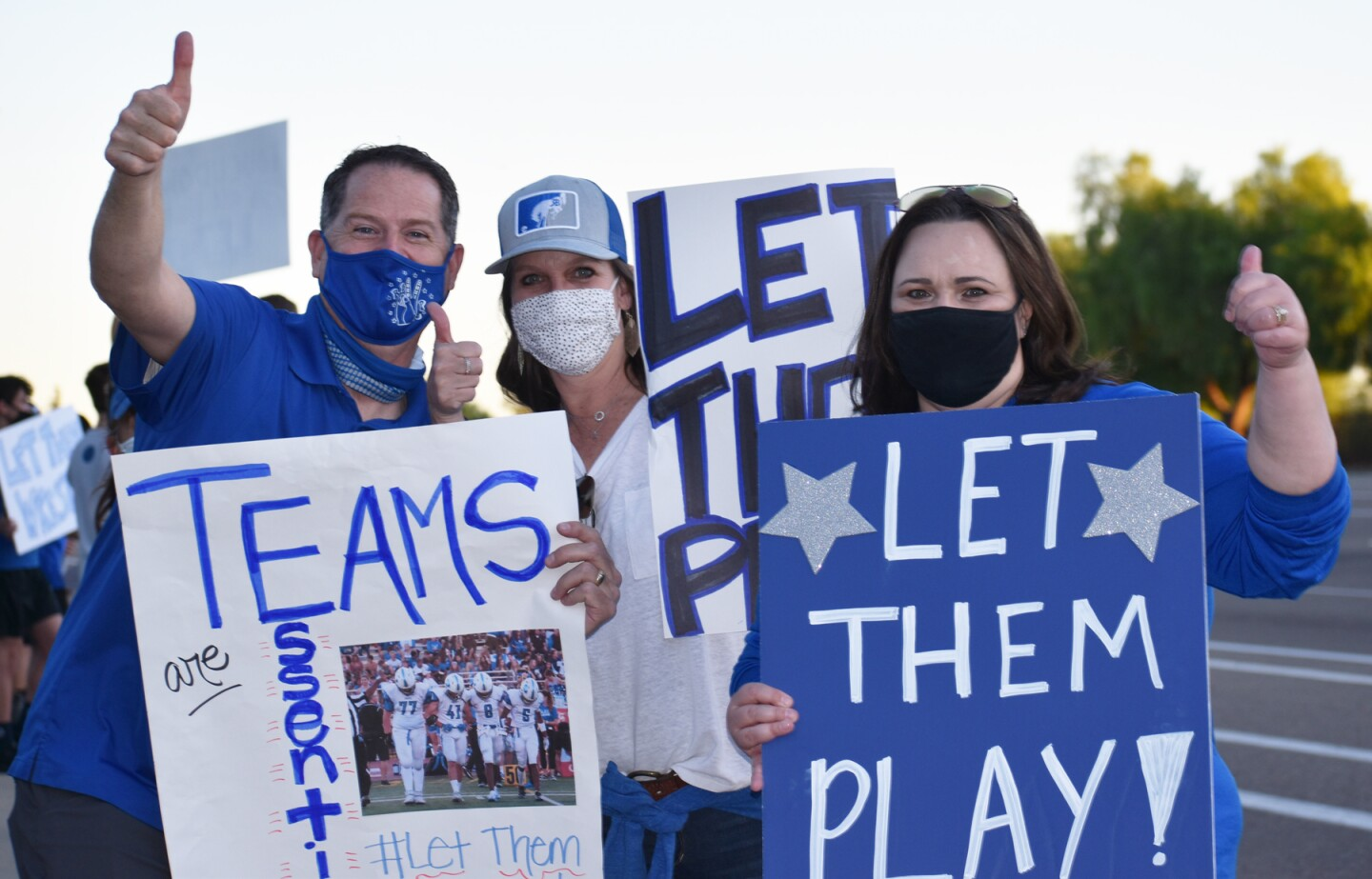"""Rancho Bernardo High parents Mark Mendenhall, Kristin Bradvica and Trish Gillaspie participating in the """"Let Them Play"""" rally."""