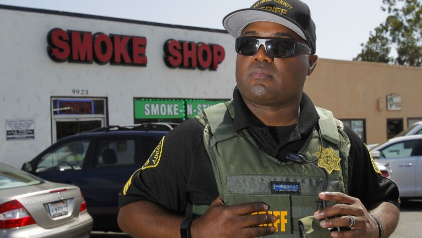 In this photo from July, sheriff's Sgt. Matthew Cook stands in front of a smoke shop on Campo Road in Casa de Oro. A marijuana dispensary operating in a commercial space adjacent to the smoke shop was raided by deputies last summer and eventually closed.