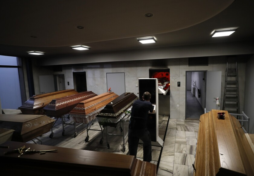 A worker moves a casket o be incinerated at a crematorium in Ostrava, Czech Republic, Thursday, Jan. 7, 2021. The biggest crematorium in the Czech Republic has been overwhelmed by mounting numbers of pandemic victims. With new confirmed COVID-19 infections around record highs, the situation looks set to worsen. Authorities in the northeastern city of Ostrava have been speeding up plans to build a fourth furnace but, in the meantime, have sought help from the government's central crisis committee for pandemic coordination. (AP Photo/Petr David Josek)