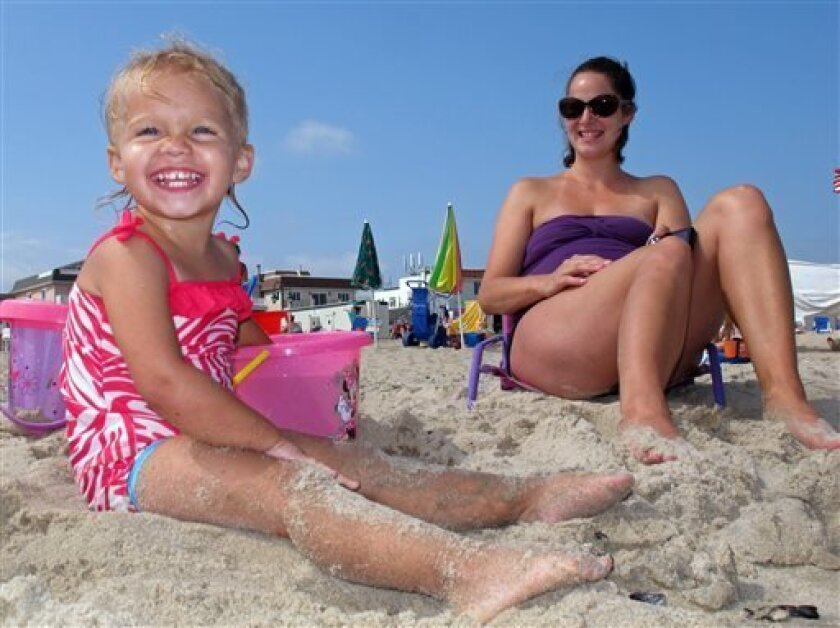 In this Aug. 29, 2013, photo, 2-year-old Addison Hunt, left, and her mother, Rachel Hunt of Nazareth, Pa. put their toes in the sand on the Belmar, N.J. beach. Business was down in parts of the shore in the first summer following Superstorm Sandy, but many merchants and vacationers say they're happ