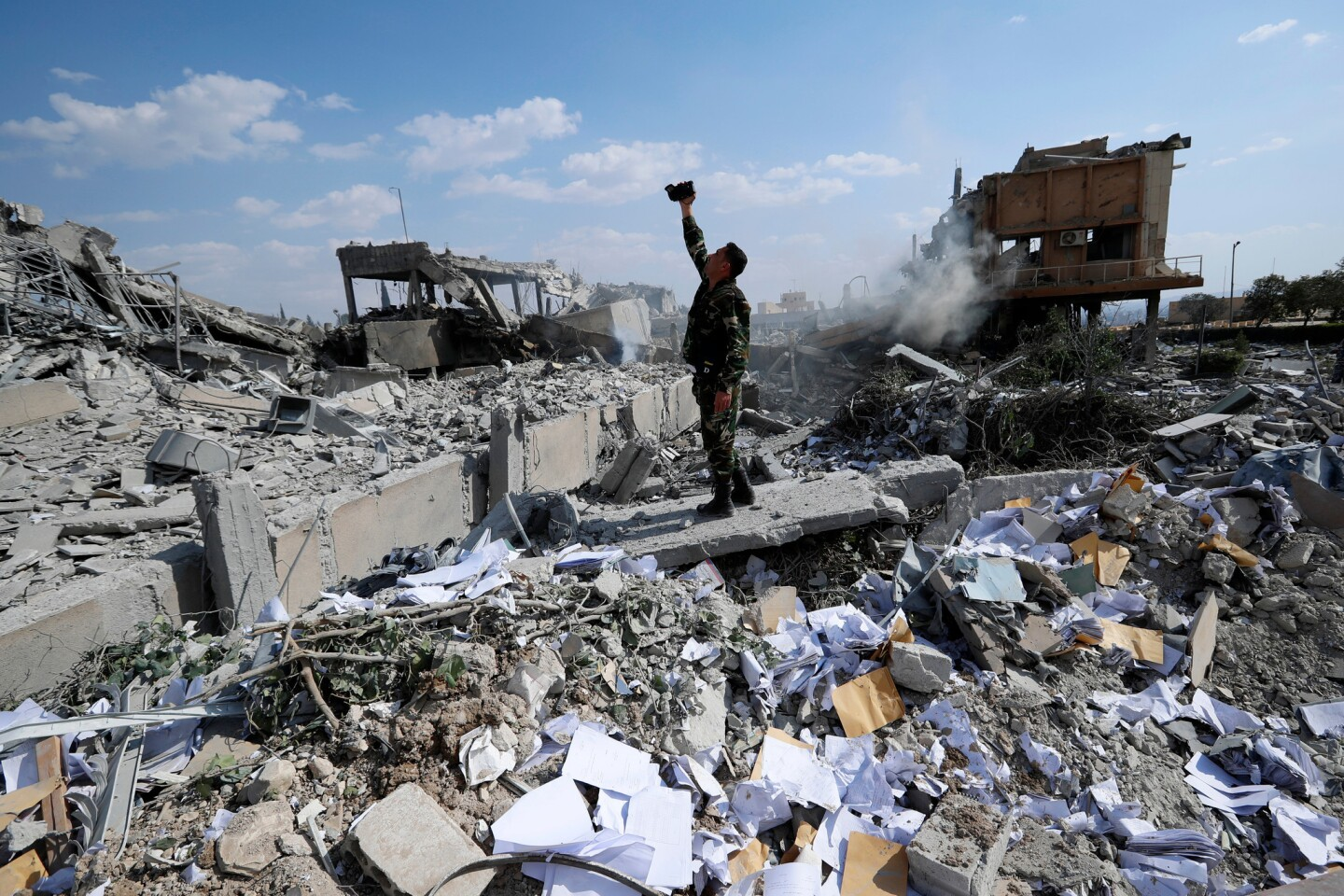 A Syrian soldier films what s left of a research center in Barzeh after U.S., French and British missiles targeted chemical facilities.