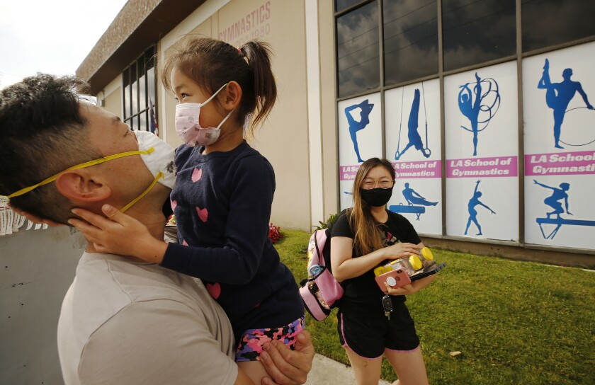 A father holds his young daughter while her mother carries supplies as they drop her off for day camp. All wear face masks.