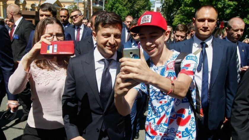 Ukrainian President Volodymyr Zelensky poses for selfies with supporters as he walks to the presidential office after his inauguration in Kiev, Ukraine, on May 20.