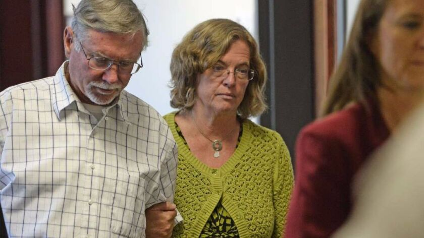Robert and Arlene Holmes, parents of Aurora theater shooting suspect James Holmes, walk from the cou