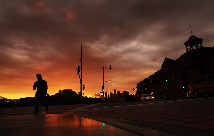 A passing storm gives way to a golden sunset as a pedestrian crosses the intersection of 1st Street and Boyle Avenue in Boyle Heights on Oct. 19, 2015. (Luis Sinco/Los Angeles Times)
