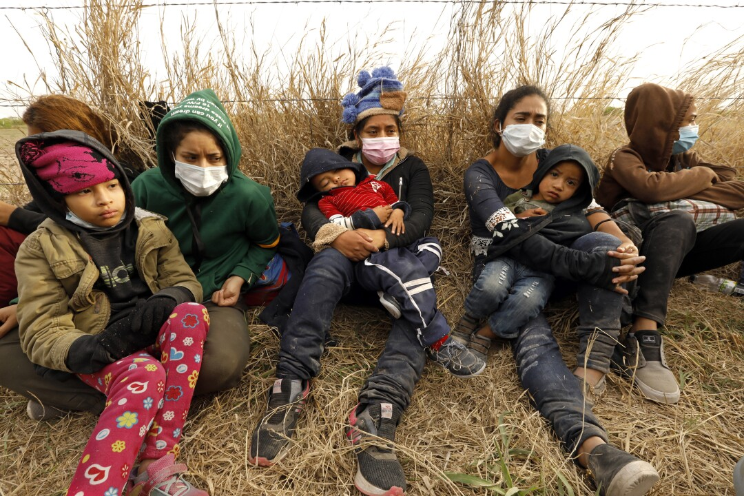 Asylum seekers rest on the ground.