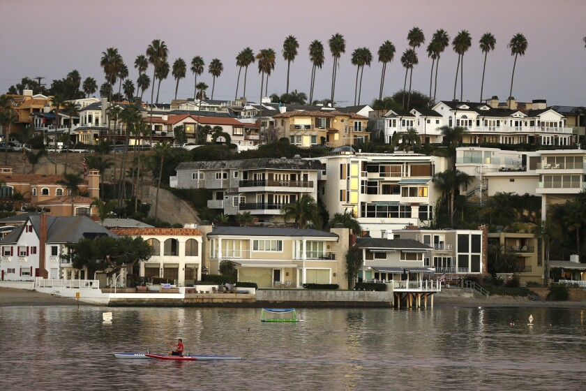 A kayaker glides through the Newport Beach harbor.