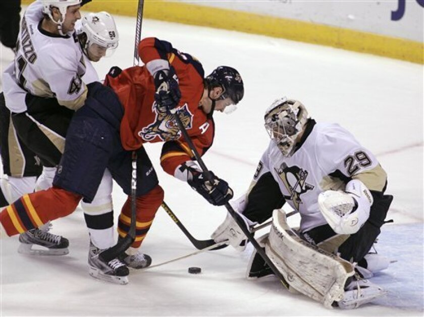 Florida Panthers' Tomas Kopecky, center, of Slovakia, looks for the puck as Pittsburgh Penguins' goalie Marc-Andre Fleury (29) defends during the second period of an NHL hockey game Tuesday, Feb. 26, 2013, in Sunrise, Fla. (AP Photo/Luis M. Alvarez)