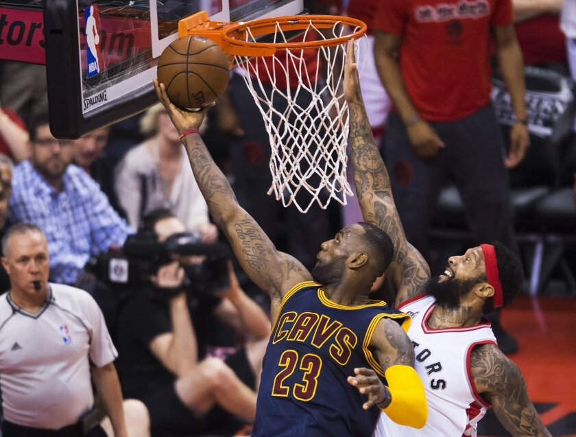 Cleveland Cavaliers forward LeBron James (23) drives past Toronto Raptors forward James Johnson during the second half of Game 6 of the NBA basketball Eastern Conference finals, Friday, May 27, 2016, in Toronto. (Nathan Denette/The Canadian Press via AP)