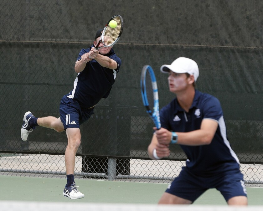 Newport Harbor's Josh Watkins gets to the ball for a forehand return in a doubles match with teammat