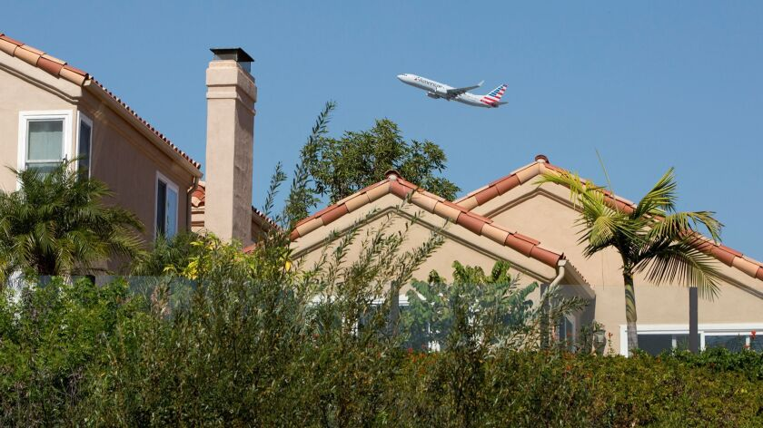An American Airlines plane flies over homes along Upper Newport Bay in Newport Beach after taking of