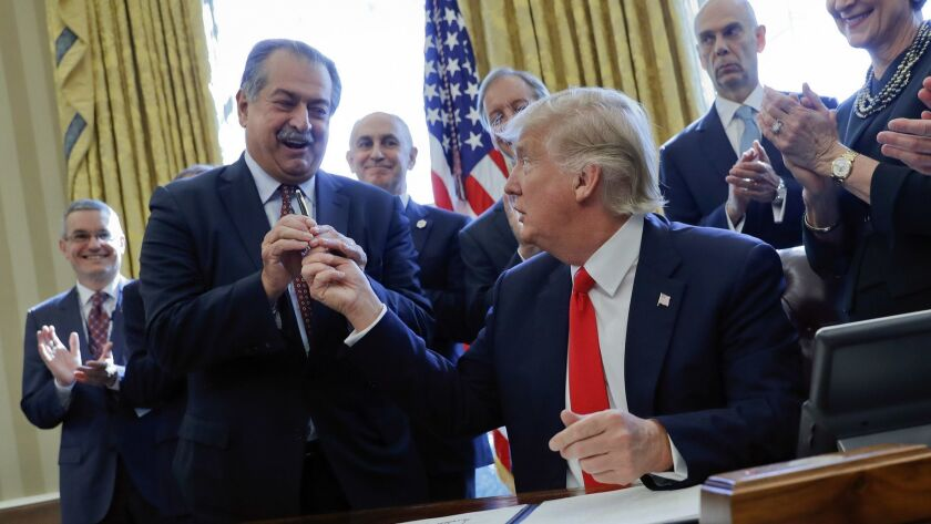 After signing an executive order in 2017, President Trump hands a pen to Andrew Liveris, then CEO of Dow Chemical. Soon after, the EPA reversed a ban on the pesticide chlorpyrifos, a Dow product.