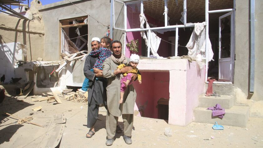 Afghans hold their injured children at a house near the scene of a suicide bomb blast in Ghazni, Afghanistan, on Sunday.