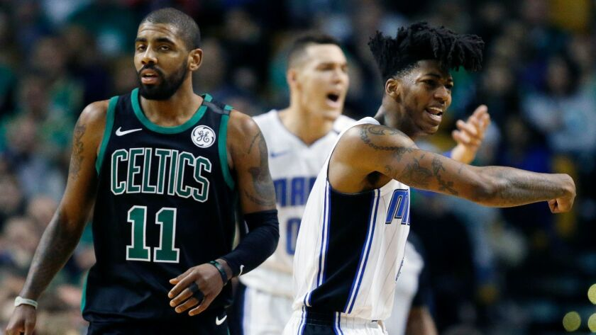 Orlando Magic's Elfrid Payton, right, and Aaron Gordon, behind, protest a call beside Boston Celtics' Kyrie Irving (11) during the first quarter.