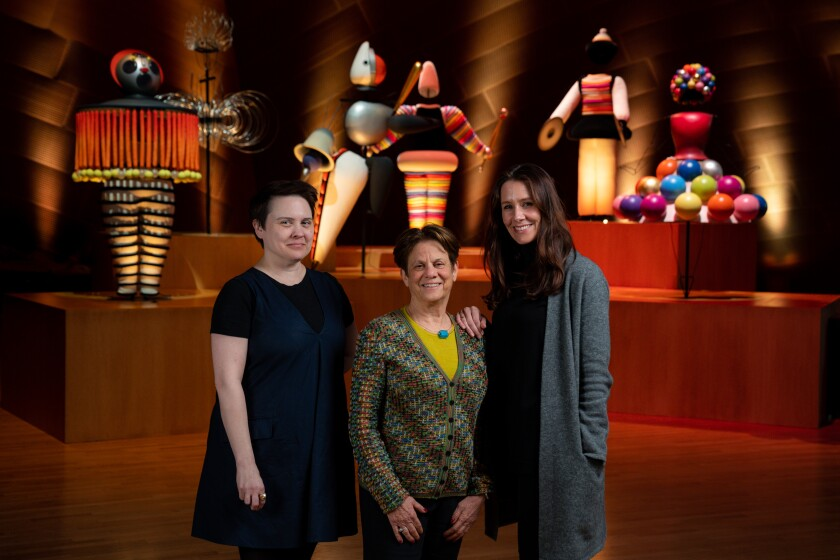 Los Angeles Philharmonic humanities director Julia Ward, left, stands with curators Stephanie Barron and Nana Bahlmann in front of designs from Oskar Schlemmer's Triadic Ballet, on display at Walt Disney Concert Hall.