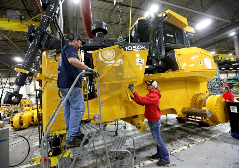 FILE - In this Wednesday, Feb. 11, 2015, file photo, Rick Ring, left, and Corinne Schmitt-Bries attach a panel to a John Deere 1050K Crawler Dozer at John Deere Dubuque Works in Dubuque, Iowa. On Friday, Feb. 12, 2016, the Commerce Department releases business inventories for December. (Jessica Rei