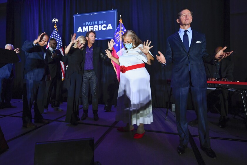 "FILE - In this July 23, 2020, file photo, from right, Faith & Freedom Coalition founder Ralph Reed, Dr. Alveda King, Journey keyboardist Jonathan Cain, and White House faith adviser Paula White-Cain, and others pray on stage during an Evangelicals for Trump campaign event titled ""Praise, Prayer and Patriotism"" in Alpharetta, Ga. President Donald Trump's reelection campaign is courting religious voters in part by seeking to portray Democrats as a threat to religious freedom — a pitch amplified by disputes over the issue during the coronavirus pandemic. (AP Photo/John Amis, File)"
