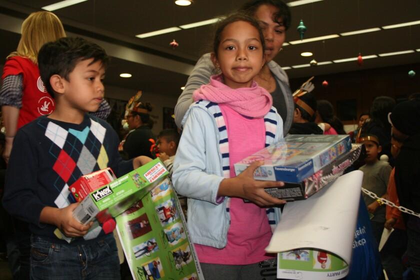 Menores reciben regalos en el 2015. Se esperan a unas 2 mil familias en el evento.