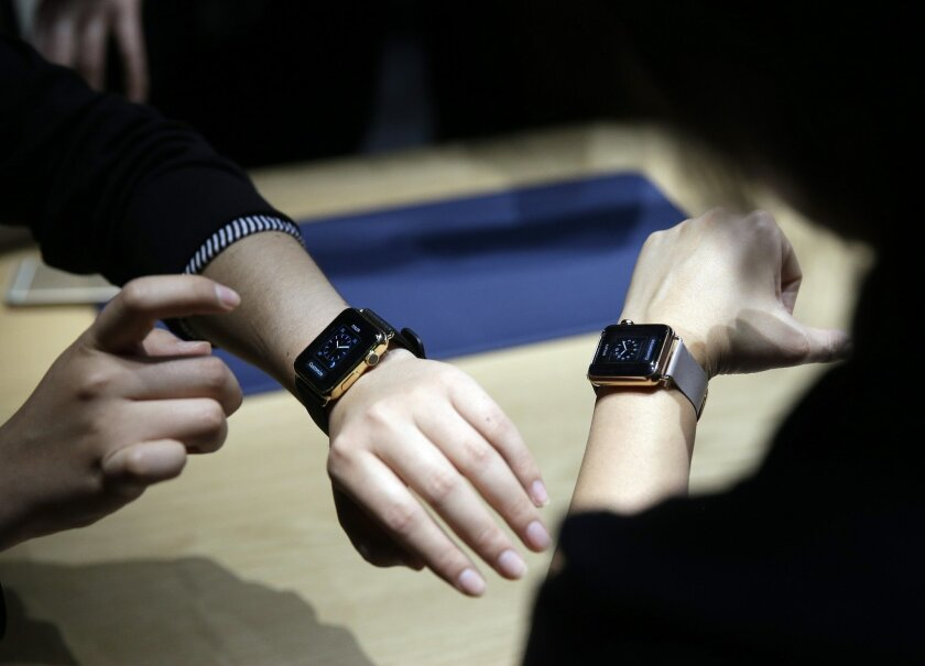 FILE - In this March 9, 2015 file photo, attendees get a look at varieties of the new Apple Watch on display in the demo room after an Apple event in San Francisco. The watchOS 2 update for Apple Watch arrives Monday, Sept. 21, 2015, delayed by nearly a week as Apple fixed an unspecified bug. (AP Photo/Eric Risberg, File)