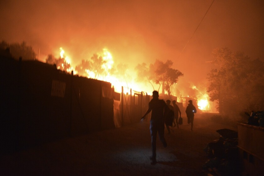 People run away as a fire burns Wednesday in the Moria refugee camp on the Greek island of Lesbos.