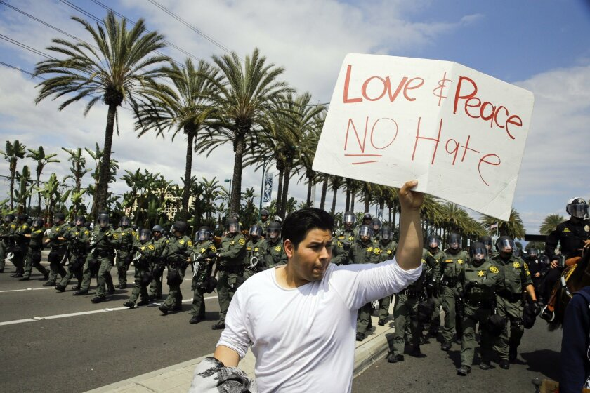 A man walks with a sign as Orange County Sheriff's deputies advance forward in riot gear to disperse protesters near the Anaheim Convention Center Wednesday, May 25, 2016, in Anaheim, after Republican presidential candidate Donald Trump held a rally at the convention center.
