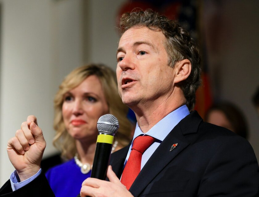 FILE - In this Feb. 1, 2016 file photo, Sen. Rand Paul, R-Ky, speaks to supporters with his wife Kelley by his side, during a caucus night victory party at the Scottish Rite Consistory in Des Moines, Iowa. Paul is dropping out of the 2016 race for president. A campaign spokeswoman confirmed his dec