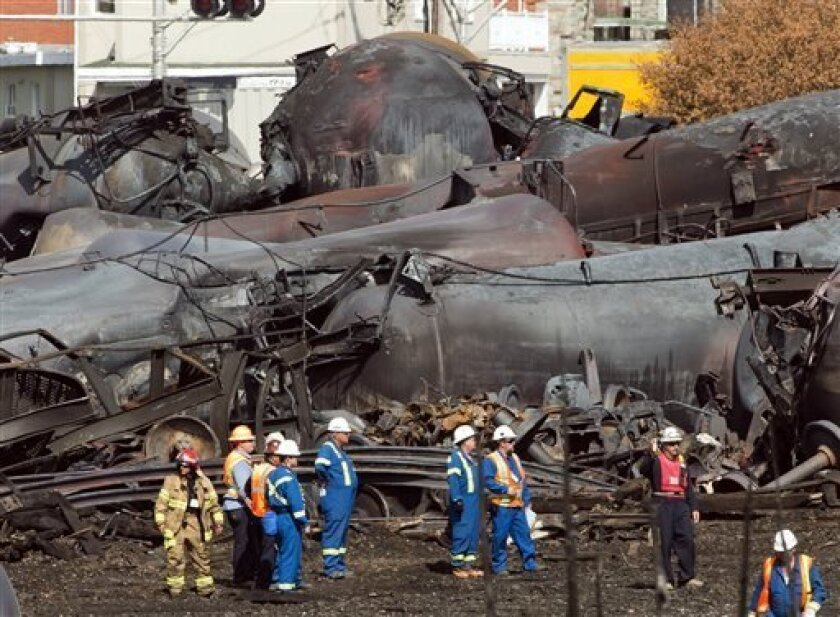 FILE - In this Tuesday, July 16, 2013 file photo, workers stand before mangled tanker cars at the crash site of a train derailment and fire in Lac-Megantic, Quebec, that happened on July 6. Canada's transportation agency said Tuesday, Aug. 13, 2013 that it has taken away the operating license of the Montreal, Maine & Atlantic Railway and its Canadian subsidiary, the U.S.-based rail company whose runaway oil train derailed and exploded in a Quebec town, killing 47 people. (AP Photo/Ryan Remiorz,