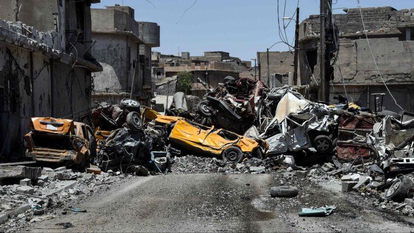 Wrecked cars clog a street in west Mosul's Zanjili neighborhood in June 2017.