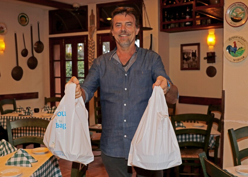 Fabio Speziali, owner of Osteria Romantica in La Jolla Shores, readies an order as the Italian restaurant now only offers takeout to help reduce the spread of the coronavirus. Commentary writer Mimi Sells encourages people to support restaurants that have stayed open for takeout as a way to strengthen community.