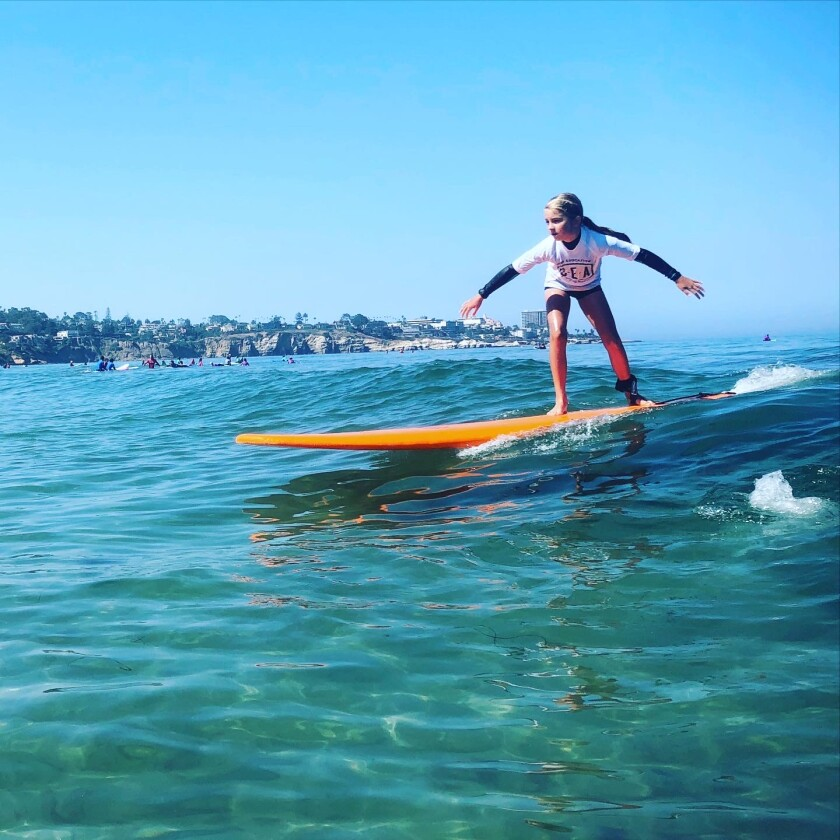 A student at the La Jolla Shores-based Surf Education Academy takes to the water.