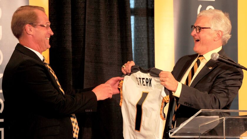 University of Missouri interim chancellor Hank Foley, right, surprises newly-appointed athletic director Jim Sterk with a football jersey with Sterk's name on it during a press conference last month in the Columns Club in Memorial Stadium.