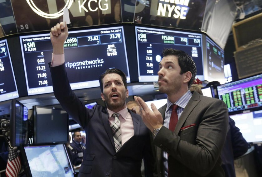 """FILE - In this Oct. 14, 2014, file photo, Jonathan Scott, left, and Drew Scott, of HGTV's """"Property Brothers"""" cable television show, mimic traders as they visit the post that handles Scripps Networks Interactive, on the floor of the New York Stock Exchange in New York. Authorities in North Dakota d"""