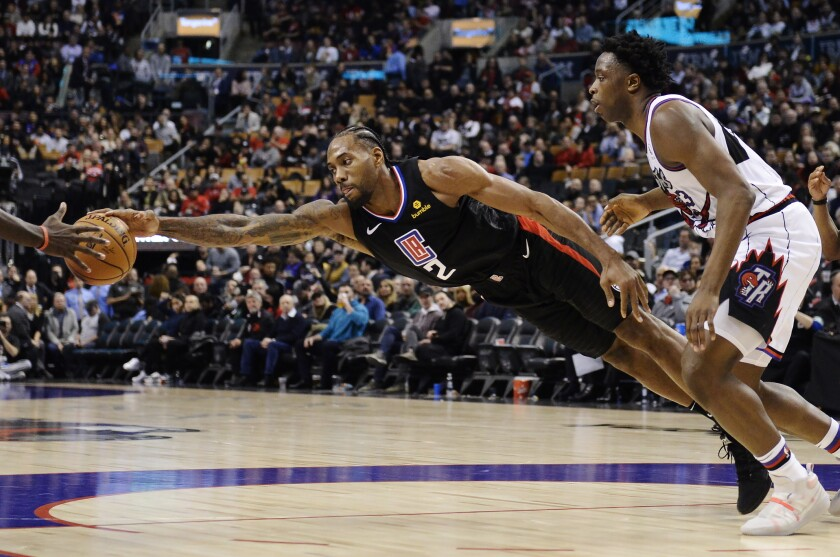 Clippers forward Kawhi Leonard (2) stretches for the ball as Raptors forward OG Anunoby (3) looks on during the second half of a game Dec. 11.